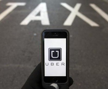 Photo illustration of logo of car-sharing service app Uber on a smartphone over a reserved lane for taxis in a street in Madrid