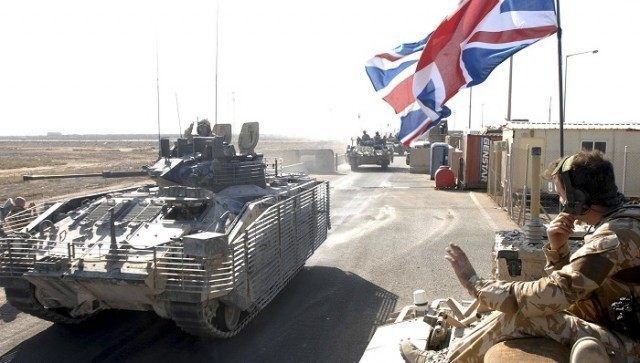 A convoy of British armoured vehicles arrive to contingency operating base after pulling out from Basra Palace, in Basra