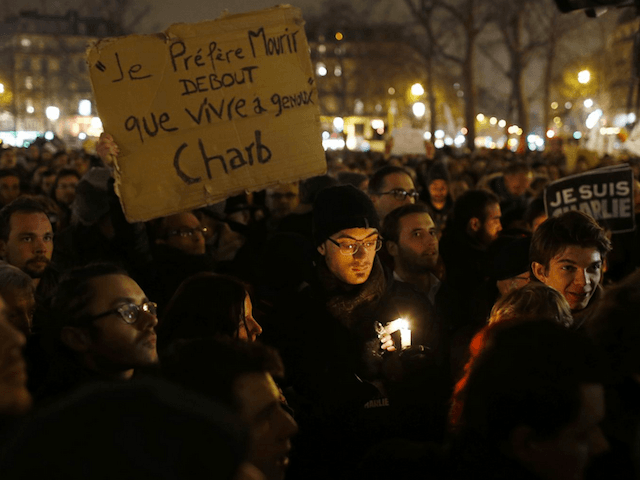 "A man holds a placard that reads, ""I prefer to die standing than live on my knees"", during a vigil to pay tribute to the victims of a shooting by gunmen at the offices of weekly satirical magazine Charlie Hebdo in Paris at Republique square January 7, 2015."