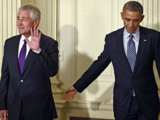 President Barack Obama reaches over to touch Defense Secretary Chuck Hagel following an announcement of Hagel's resignation.