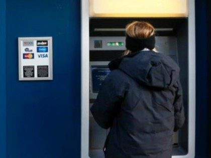 FILE - In this Jan. 5, 2013 file photo, a woman uses an ATM machine in downtown Pittsburgh.