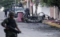 Mexican policemen and a soldier stand guard next to remains of a parked vehicle outside a studio of top broadcaster Televisa in Ciudad Victoria