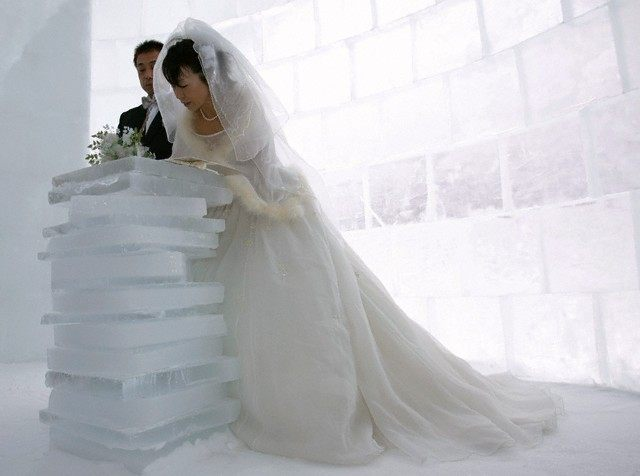 Kito signs covenant as groom Matsuoka looks on during their wedding ceremony inside chapel made of ice in Shikaoi town, northern Japan