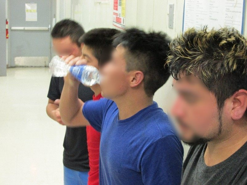 Four Captured Illegal Immigrants Receive Water While Being Processed - Photo Courtesy of U.S. Border Patrol