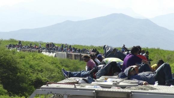 People hoping to reach the U.S. ride atop the wagon of a freight train, known as La Bestia (The Beast) in Ixtepec