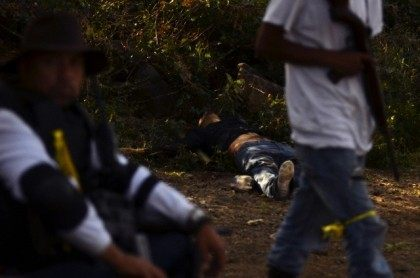 Members of the community police walk near a deceased member of the Knights Templar cartel (Caballeros Templarios) after a clash in Michoacan state