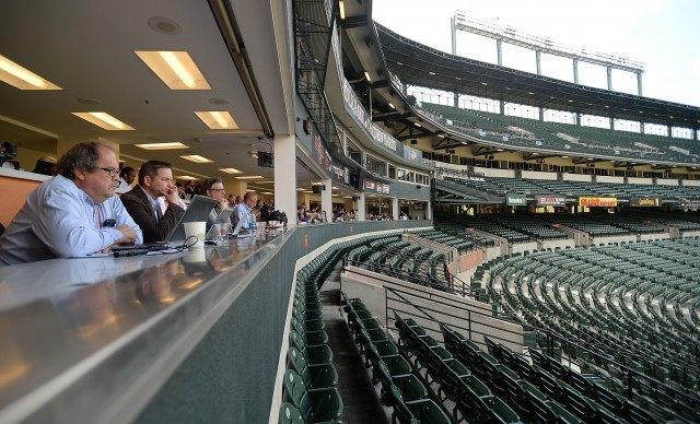 Reporters watch from the press box as the Baltimore Orioles and the Chicago White Sox play a baseball game in a fan less stadium Wednesday, April 29, 2015, in Baltimore. Due to security concerns the game was closed to the public. A state of emergency was issued Monday after riots erupted following the funeral of Freddie Gray.(AP Photo/Gail Burton)