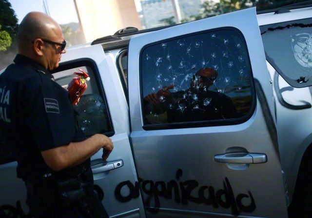 A federal police officer holds a fire extinguisher as he stands next to the vandalized vehicle of Acapulco's Mayor Luis Walton Aburto after a demonstration demanding justice for the 43 missing students from Ayotzinapa Teacher Training College, in Aca