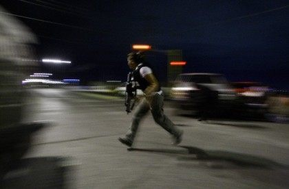 Police detective runs for cover during a police operation to regain control of a jail in Ciudad Juarez