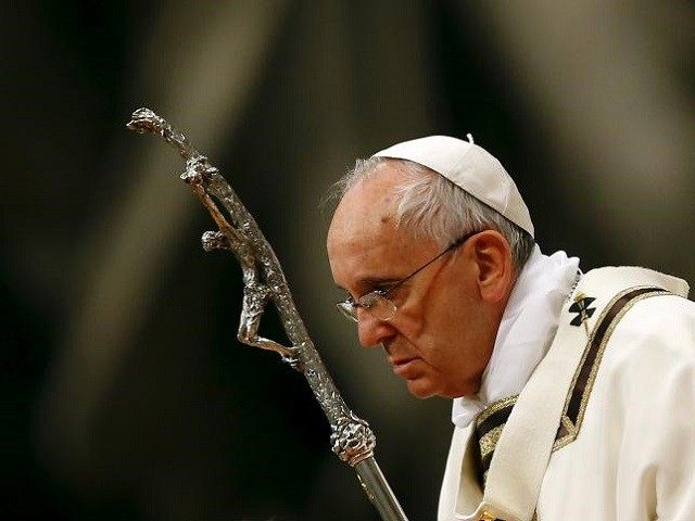 Pope Francis holds a crucifix as he lead the Easter vigil mass in Saint Peter's basilica at the Vatican