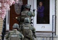 File photo of a member of the SWAT team motioning to a resident to come out of the house as they conduct a house to house search for Dzhokar Tsarnaev, the one remaining suspect in the Boston Marathon bombing, in Watertown