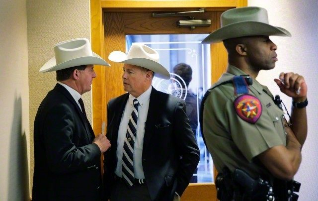"Jackson County Sheriff A.J. ""Andy"" Louderback, left, confers with Chambers County Sheriff Brian Hawtohorne, center, before giving testimony at a hearing where lawmakers discussed whether to legalize concealed handguns on college campuses and open carry everywhere else on Thursday, Feb. 12, 2015, in Austin, Texas."