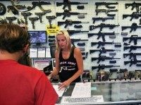 In this July 20, 2014 photo, with guns displayed for sale behind her, a gun store employee helps a customer at Dragonman's, east of Colorado Springs, Colo. When Colorado lawmakers expanded background checks on firearms last year, they were expecting a huge increase. But the actual number the first 12 …