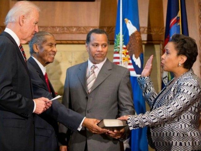 Vice President Joe Biden, accompanied by Loretta Lynch's father Lorenzo Lynch, second from left, and Loretta Lynch's husband Stephen Hargrove, second from right, administers the oath of office to Loretta Lynch as the 83rd Attorney General of the U.S., Monday, April 27, 2015, during a ceremony at the Justice Department …