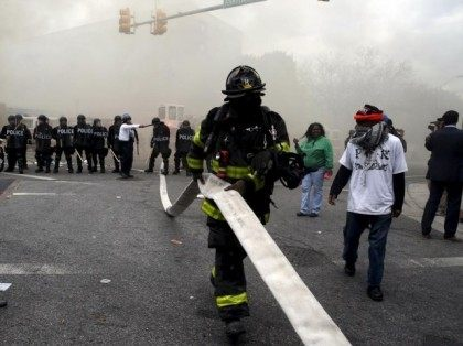 A Baltimore firefighter pulls a hose through crowds of protestors, who later cut the hose, in front of a burning building during clashes in Baltimore