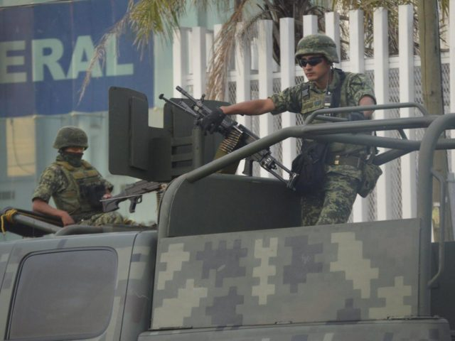 Mexican soldiers guard the Federal Police building in Matamoros following a grenade attack by cartel members.