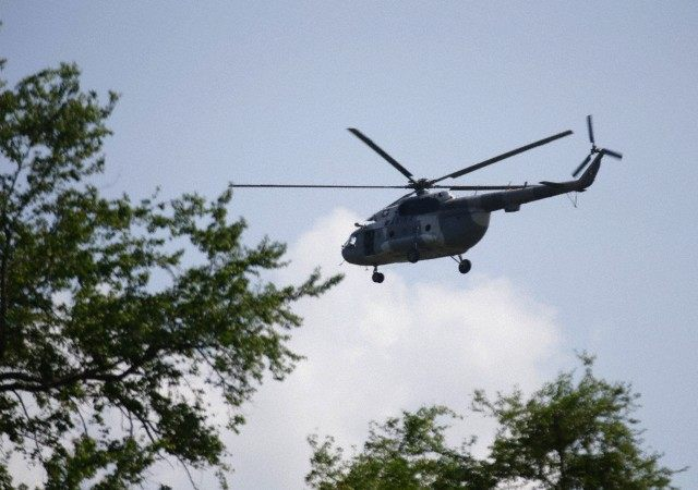 A Mexican Navy helicopter flies overhead during a search for human remains on a river near a new mass grave discovered outside the mountain town of Cocula
