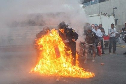 A police officer tries to fight the flames surrounding him after protesters began throwing Molotov cocktails and spraying gasoline at police in Mexico City.