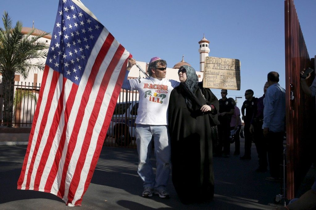"""Two demonstrators stand in front of Islamic Community Center to oppose """"Freedom of Speech Rally Round II"""" across street in Phoenix, Arizona"""