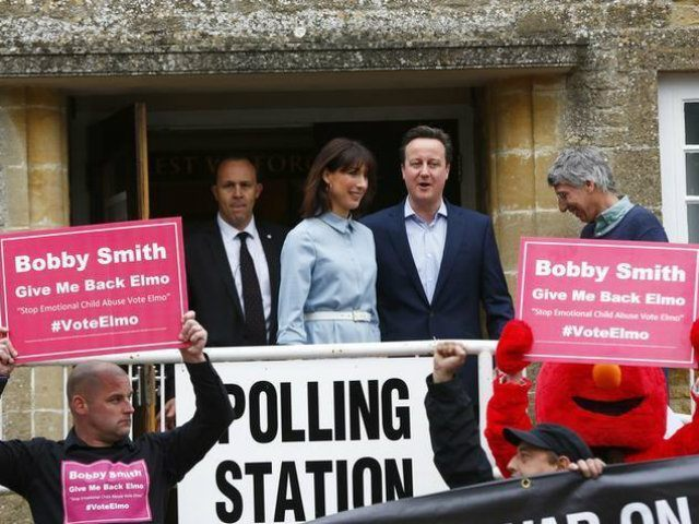 Protesters hold up placards and a banner as Britain's Prime Minister David Cameron and his wife Samantha leave a polling station after voting in Spelsbury (REUTERS/Eddie Keogh)