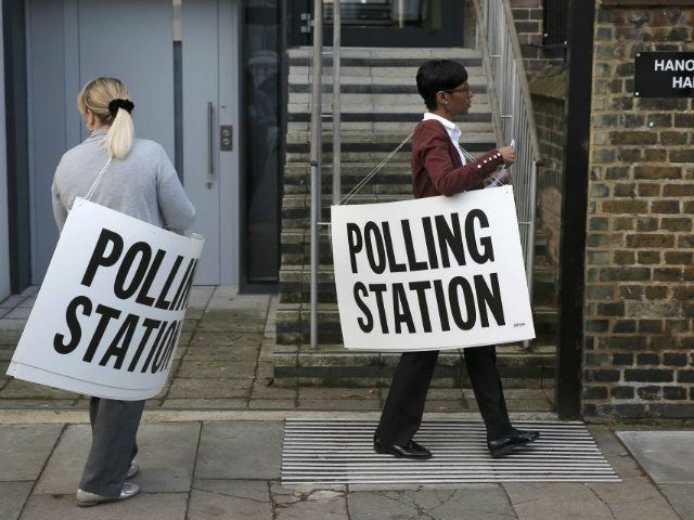 Polling station workers place signs outside a polling station in Islington, in readiness for voting in Britain's general election, in London (REUTERS/Peter Nicholls)