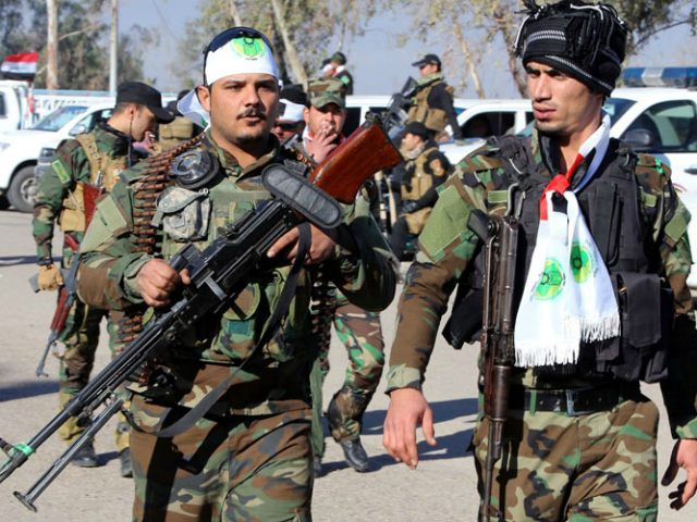 """IRAQ, KHALIS : Iraqi Shiite fighters walk at Camp Ashraf (a former base of Iran's opposition People's Mujaheddin Party) during a ceremony to mark the liberation of Iraq's Diyala province from the Islamic State group's control, in Khalis, in the Diyala province, on February 2, 2015. Iraqi forces have """"liberated"""" …"""
