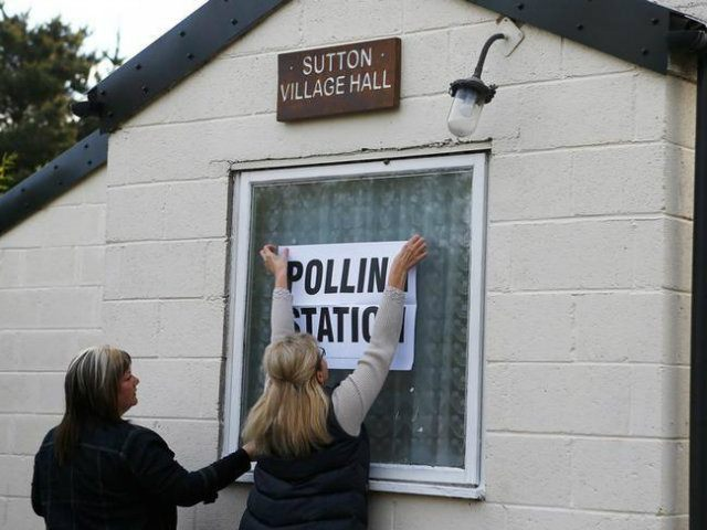 Electoral workers put up a sign in the window of a building being used as a polling station in Doncaster