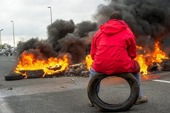 A striking employee of the French company My Ferry Link, a cross-channel ferry service, sits on a tyre in front of tyres set on fire as he takes part in a blockade of the access to the Channel Tunnel on June 23, 2015 in Calais, northern France. AFP PHOTO PHILIPPE HUGUEN
