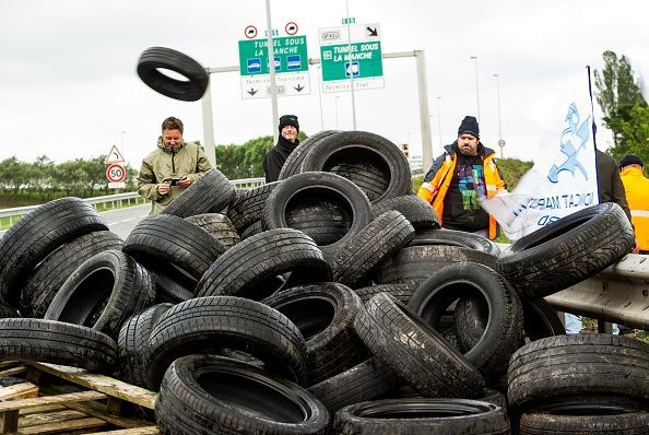 Striking employees of the French company My Ferry Link, a cross-channel ferry service, prepare to  set tyres on fire to block the access to the Channel Tunnel on June 23, 2015 in Calais, northern France. AFP PHOTO PHILIPPE HUGUEN