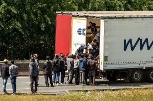 Migrants climb in the back of a lorry on the A16 highway leading to the Eurotunnel on June 23, 2015 in Calais, AFP PHOTO / PHILIPPE HUGUEN