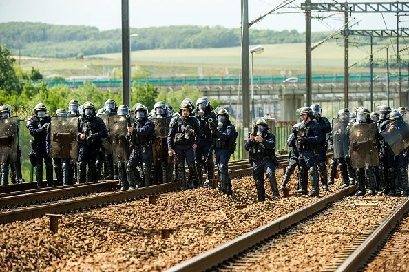 "French riot police officers take position to drive out protesting French employees (unseen) of the company English Channel passenger and freight ferry company ""MyFerryLink"", who block the railway tracks of the Eurostar Channel tunnel line, on June 23, 2015 in Calais, northern France. Eurotunnel said that train services had been …"