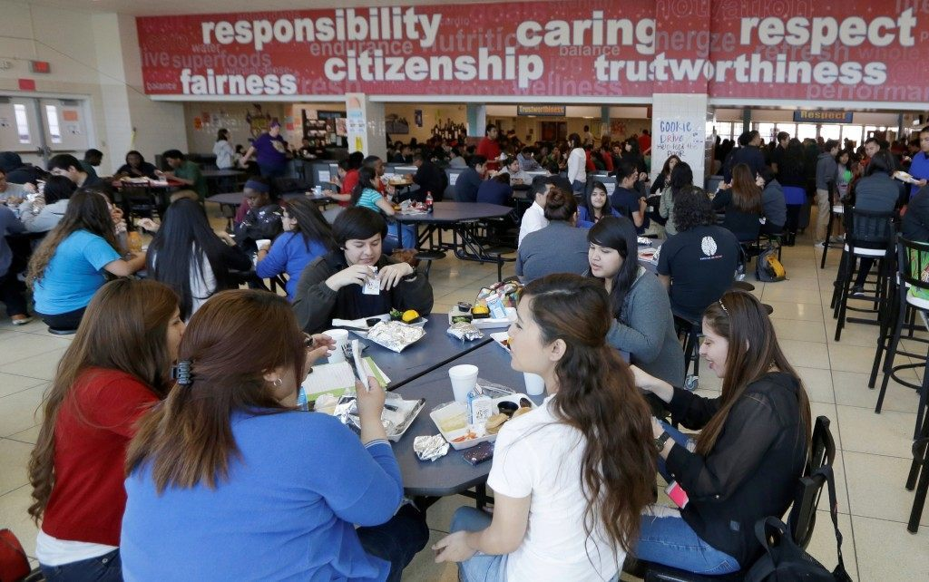 Students eat their lunch in the cafeteria at Thomas Jefferson High School in Dallas,  (AP Photo/LM Otero)