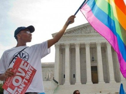 Carlos McKnight holds up a flag in support of gay marriage outside of the Supreme Court in Washington, June 26, 2015.