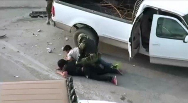 A Mexican soldier arrests two suspected cartel members