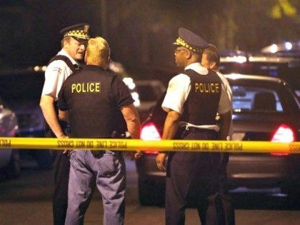 CHICAGO, IL - JUNE 17: Police investigate the scene where a 15-year-old boy was shot and killed by police after he reportedly pointed a gun at officers during a foot chase on June 17, 2013 in Chicago, Illinois. Two pistols were reported to have been found on the boy after …