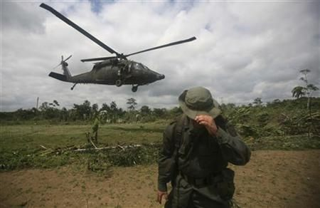 Colombian police officer protects himself from wind as helicopter takes off from coca plantation in La Espriella near Tumaco