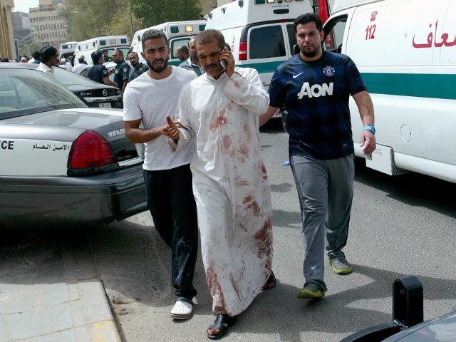 Kuwaiti men accompany a man with blood-stained clothes at the site of a suicide bombing that targeted the Shiite Al-Imam al-Sadeq mosque. AFP PHOTO / YASSER AL-ZAYYAT