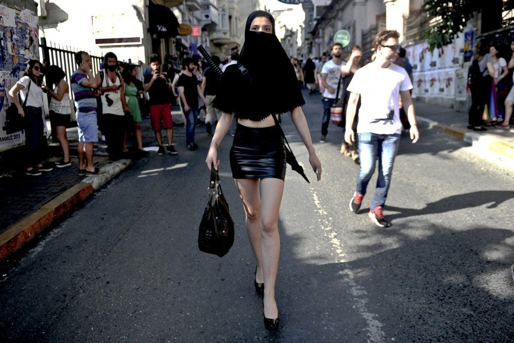 A woman wearing a costume walks away from Turkish riot police during the Gay Pride parade on June 28, 2015 in the Istiklal street near the Taksim square in Istanbul. (OZAN KOSE/AFP/Getty Images)