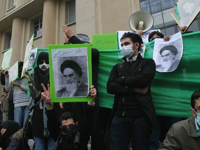 Iranian opposition supporters hold pictu
