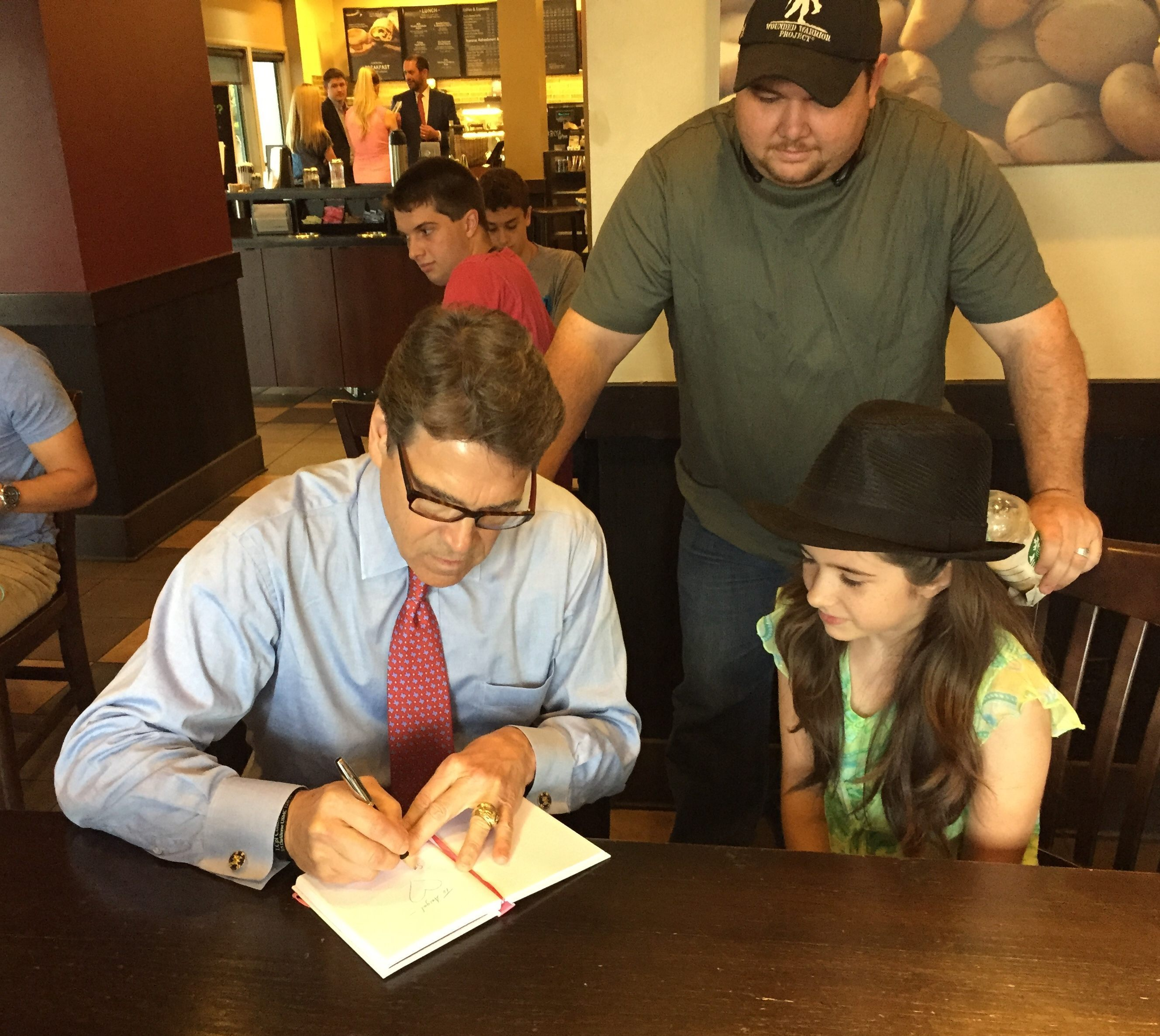 Gov. Perry signs an autograph for a young fan. Photo by Sarah Rumpf.