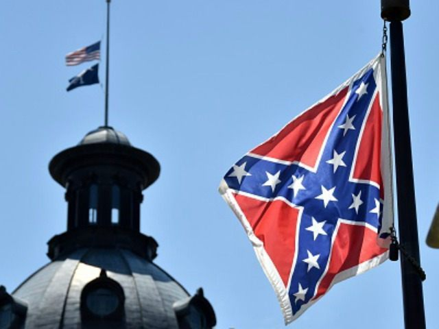 The South Carolina and American flags flying at half-staff behind the Confederate flag erected in front of the State Congress building in Columbia, South Carolina on June 19, 2015. Police captured the white suspect in a gun massacre at one of the oldest black churches in Charleston in the United …