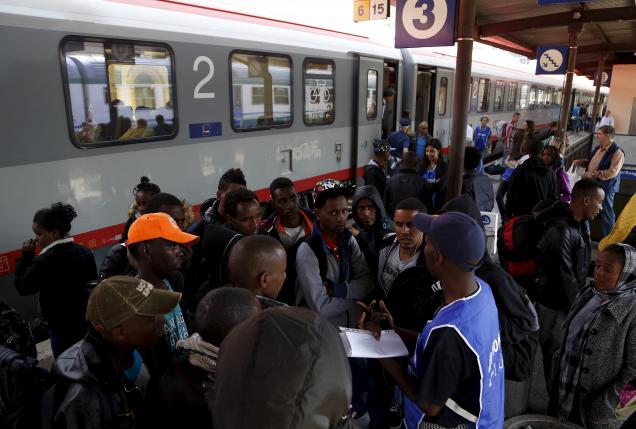 A volunteer talks to a group of migrants as police officers stand in front of the door of a train bound for Munich at the Bolzano railway station