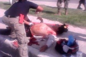 Medical personnel tend to a bystander his by grenade shrapnel in the border city of Matamoros.
