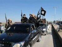 In this photo released on May 4, 2015, by a militant website, which has been verified and is consistent with other AP reporting, Islamic State militants pass by a convoy in Tel Abyad town, northeast Syria. In contrast to the failures of the Iraqi army, in Syria Kurdish fighters are …