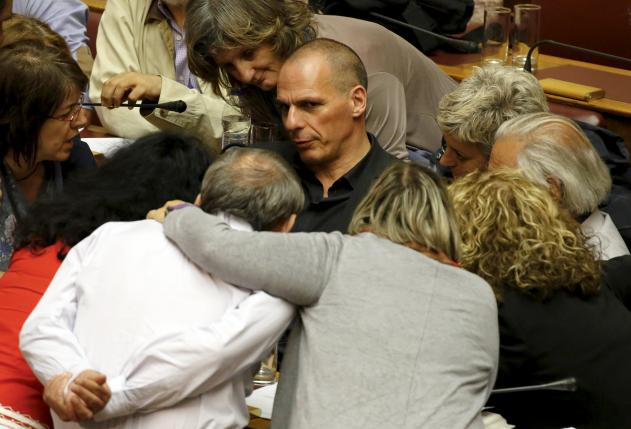 Greek Finance Minister Varoufakis is surrounded by lawmakers during a parliamentary session in Athens