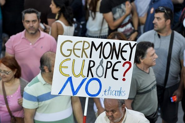 'NO' protester supporter holds a banner as they gather in front of the parliament building in Athens on July 3, 2015.