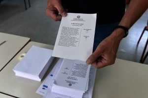A polling station official shows a ballot at a polling station in Athens on the eve of the greek referendum on July 4, 2015. Nearly 10 million Greek voters will take to the ballot booths on July 5 to vote 'Yes' or 'No' in a referendum asking if they accept more austerity measures in return for bailout funds