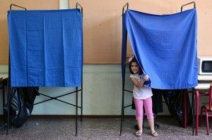 "A childs peers out from a booth at a polling station in Athens, on July  5, 2015. Beleaguered Greeks headed to the polls to choose between ""being devoured by a lion or a wolf"" in a bailout referendum many see as an impossible decision with unknown consequences for their crisis-wracked country"