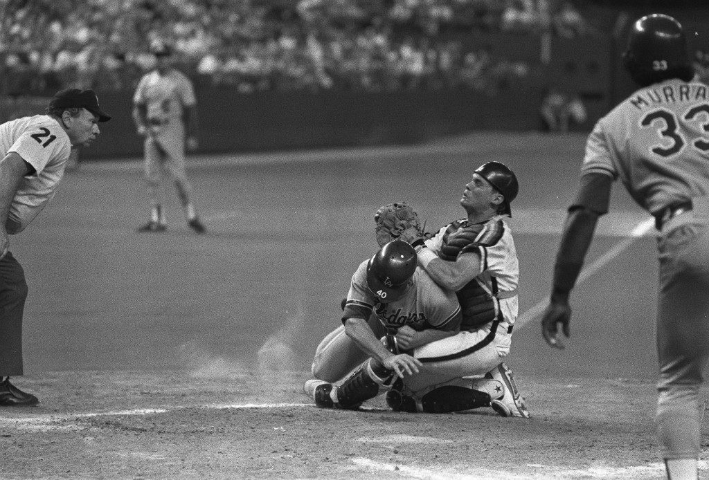 **FILE** Los Angeles Dodgers' Billy Bean (40) collides with Houston Astros catcher Craig Biggio at home plate in the fifth inning of their baseball game in this Sept. 5, 1989 file photo in Houston. Dodgers' Eddie Murray looks on at right. Biggio plans to retire at the end of the season after a 20-year career in which he joined the elite 3,000-hit club, he announced Tuesday, July 24, 2007. (AP Photo/Tim Johnson, File)