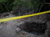 FILE - In this Oct. 6, 2014 file photo, clandestine graves are taped off after 28 bodies were found in them near Iguala, Mexico. Mass graves are regularly found around the country _ 11 bodies in August in Michoacan state, 19 others in Iguala just last May. (AP Photo/Eduardo Verdugo)